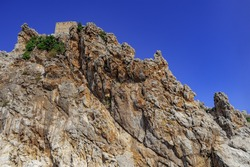 The peak of the rock with the wall of the Alanya Castle at the top (Turkey). Rough stone clump against the blue sky, close-up