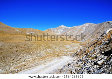 the peaks of Mount Olympus in clear weather without clouds (Mitikas Peak, 2 918 m). Gray mountains, rocks, yellow lichens - the road to Olympus on a sunny day on the West Side. National park of Greece Stock fotó ©