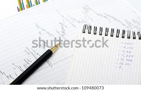 The pen and financial report. A workplace of the businessman