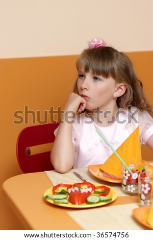 The pensive girl has breakfast in a cafe