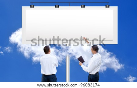 The people against a publicity board and the bright blue cloudy sky