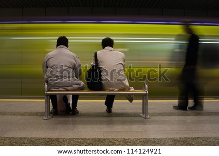 The people are waiting the subway in the station. - stock photo