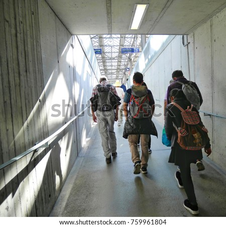 The people are walking at the subway public satation of train.Asain girl is walking,has backpack no brand.Sign language germany #759961804