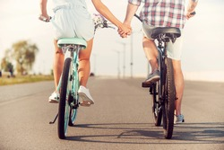 The perfect summer date. Rear view of young couple holding hands while riding on bicycles along the road