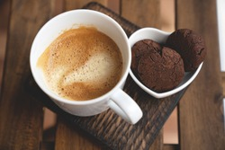 The perfect tasty breakfast Chocolate cookies with dark chocolate and sea pink Himalayan salt and cup of coffee on a wooden background