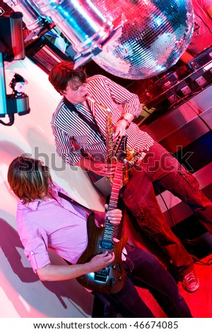 The performance of a saxophonist and a guitarist in a nightclub.