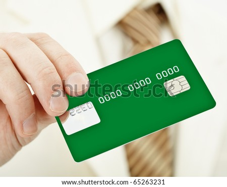 The person holds a green electronic plastic card in a hand