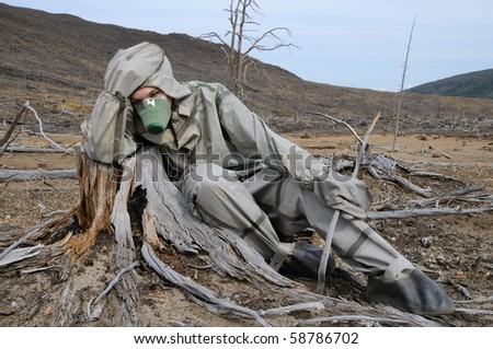 The person in protective suit in the dead forest