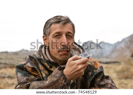 The person in rest smokes against mountain landscape