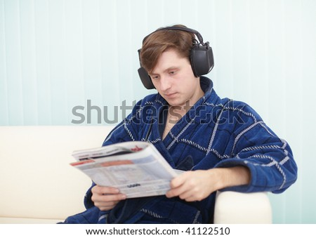 The person in the big ear-phones sits on a sofa reads the newspaper