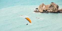 The person is engaged in paraglayding. It flies on paraplane or parachute of orange color against the background of beautiful rocks and the blue sea.