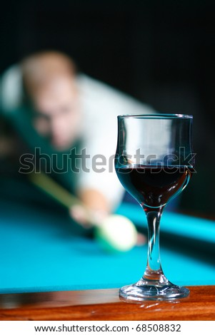 The person playing club behind a billiard table driving spheres