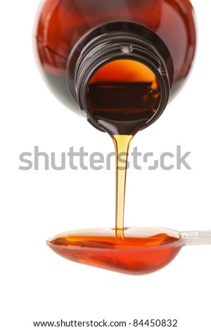 The person pours a syrup in a spoon, isolated on white