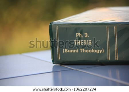 The Ph.D. thesis of Sunni Theology from the Faculty of Theology lay on the blue tile floor. #1062287294