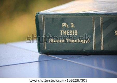 The Ph.D. thesis of Sunni Theology from the Faculty of Theology lay on the blue tile floor. #1062287303