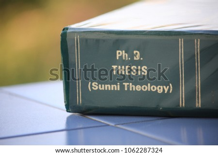 The Ph.D. thesis of Sunni Theology from the Faculty of Theology lay on the blue tile floor. #1062287324