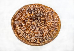 The Phaistos Disc (also spelled Phaistos Disk, Phaestos Disc)  isolated on white background covered on both sides with a spiral of stamped symbols.