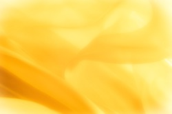 The photo is blurred. Texture, background, pattern. Yellow silk fabric. Abstract background of luxury Yellow fabric or liquid wave or wavy grunge texture. The whole background.