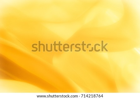 The photo is blurred. Texture, background, pattern. Yellow silk fabric. Abstract background of luxury Yellow fabric or liquid wave or wavy grunge texture. The whole background. - Shutterstock ID 714218764