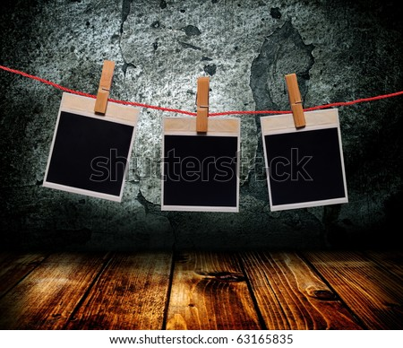 The photo of a frame hang on clothespins in an old interior.