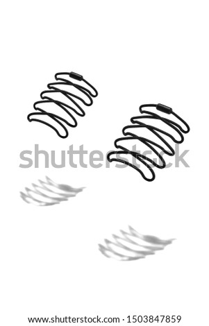 The photo of black shoelaces with black tips, hanging in the air on a white background. Shoelaces is casting a shadow.