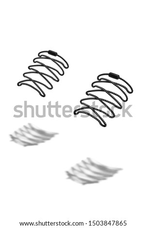 The photo of black spotted shoelaces with black tips, hanging in the air on a white background. Shoelaces is casting a shadow.