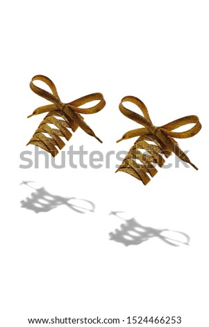 The photo of golden shiny shoelaces with violet tips, hanging in the air on a white background. Shoelaces is casting a shadow.
