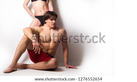 The photo of the guy's muscles, the girl against his background in his own way underlines the relief of his muscles. fitness culture. healthy lifestyle. This photo is for your project. Handsome man