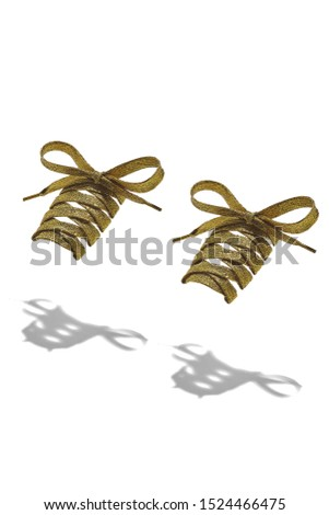 The photo of yellow shiny shoelaces with yellow tips, hanging in the air on a white background. Shoelaces is casting a shadow.