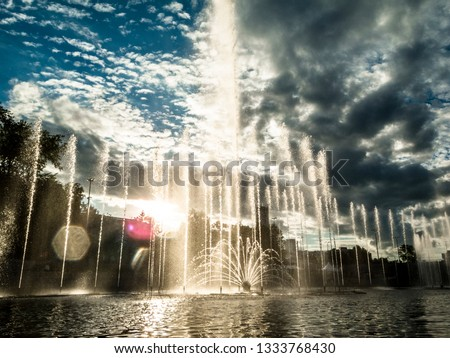 The photo renders the dancing of a fountain to classical music at sunset. #1333768430