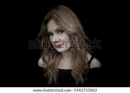 The photo shows a beautiful female model of middle age in black on a black background close-up in full face. Charming woman with long hair  is charmingly smiling.