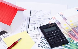 The photo shows a model house on an expose with calculator, money and a pen
