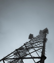 The photo shows a telecommunication tower made of metal. The antenna is high enough and goes up into the foggy sky. Additional equipment and devices are located on the antenna.