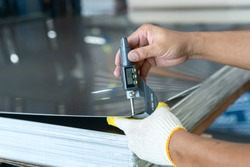 The photo shows how to measure how thick of the metal sheet by using digital thickness gauge.