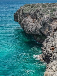 The photo shows the Atlantic Ocean with a rocky coast. The exotic island's beach contains many rocks and grottoes. The rocky landscape and the sea are a great vacation spot.
