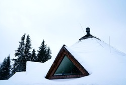 The photo shows the snow-covered roof of a wooden house in the mountains with a triangular window