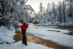 The photographer does to a photo the wild nature at sunset, the wild frozen small river in the winter wood, the Red River, ice, snow-covered trees