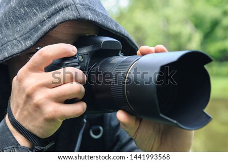 The photographer hidden with the camera. A man in a hood is taking pictures hidden.