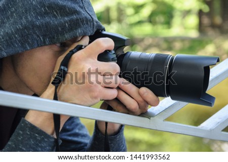 The photographer hidden with the camera. A man in a hood is taking pictures hidden.A man in a hood is taking pictures hidden.