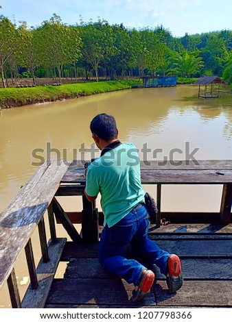 The photographer is taking a knife on a wooden bridge. #1207798366