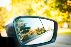 the photographer takes a picture of himself in car mirror