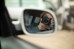 The photographer takes pictures of himself in the mirror. Using the camera in the car. Looking through the lens in the rearview mirror. Self-portrait of the photographer.