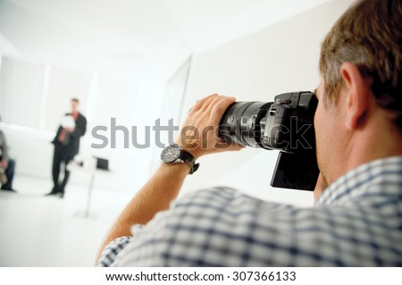 The photographer takes pictures of people in a professional photo studio