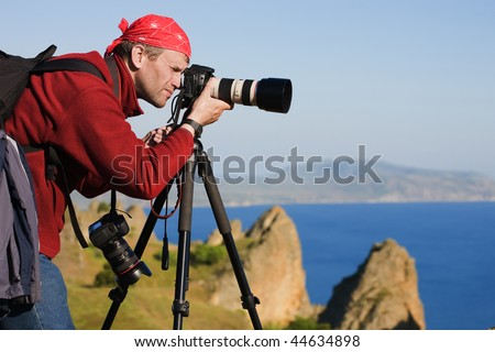 The photographer with the camera on a tripod. On a background the sea and rocks