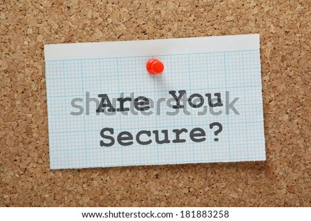 The phrase Are You Secure typed on a piece of graph paper and pinned to a cork notice board