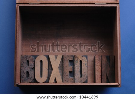 the phrase \'boxed in\' in wood type inside a wood box
