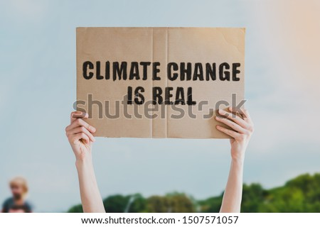 The phrase ' Climate change is real ' drawn on a carton banner in men's hand. Human holds a cardboard with an inscription: Climate change is real Foto stock ©