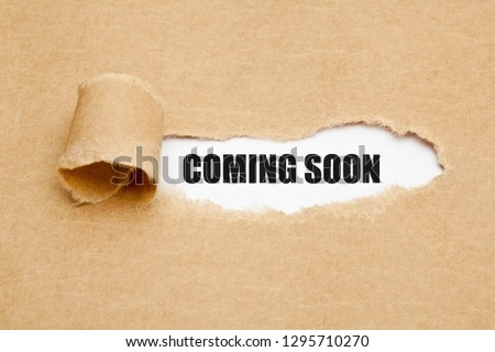 The phrase Coming Soon appearing behind ripped brown paper. Concept about upcoming promising event approaching in near future. Сток-фото ©