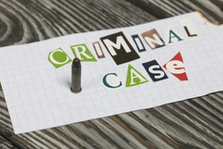 The phrase Criminal case made of letters cut from a magazine and pasted on a sheet of paper. Nearby lies a small caliber cartridge. On brushed pine boards painted black and white.