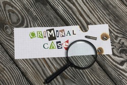 The phrase Criminal case made of letters cut from a magazine and pasted on a sheet of paper. Nearby lies a small caliber cartridge and a magnifying glass.